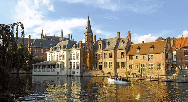 Die historischen Häuser spiegeln sich in einer Gracht, Bootspassagiere genießen den Anblick.